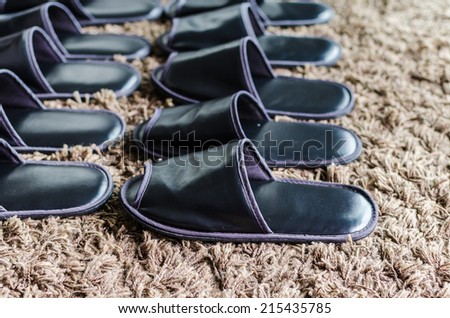 row of black slippers on carpet - stock photo