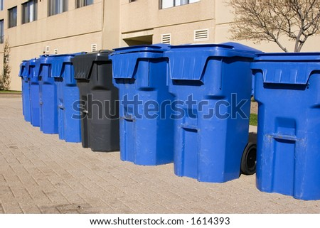 Row of blue garbage bins with one black bin beside an apartment building
