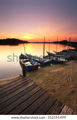 Row of boats parked during calm sunrise at Lumut Perak. Soft focus due to long exposure shot. Nature composition.