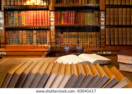 Row of book in front of desk in classic library - stock photo