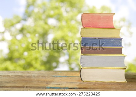 row of books against nature background, reading and summer concept - stock photo