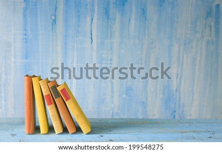 row of books on grungy background, free copy space - stock photo