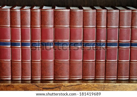 row of books with brown cover on a shelf