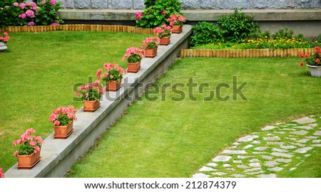 Row of boxes with pink geranium flowers in French garden.