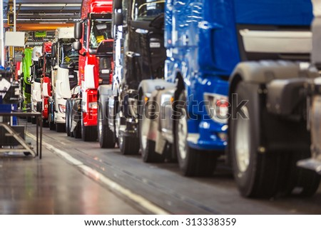 Row of brand new, shiny, trucks in various colours, ready to come off a production line in a truck factory - stock photo