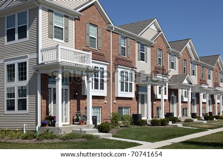 Row of brick townhouses with covered entries - stock photo
