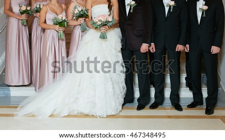 Row of bridesmaids and groomsmen at big wedding ceremony