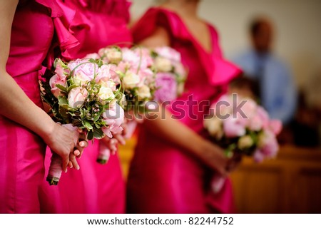 Row of bridesmaids with bouquets at wedding ceremony - stock photo
