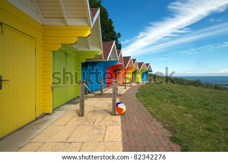 Row of bright colored beach huts on summer day with blue sky. Beach ball at one of the hut doors. - stock photo