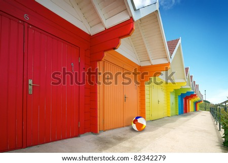 Row of bright colored beach huts on summer day with blue sky. Beach ball at one of the hut doors.