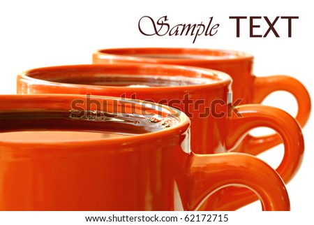 Row of bright orange mugs filled with coffee or tea on white background with copy space.  Macro with shallow dof. - stock photo
