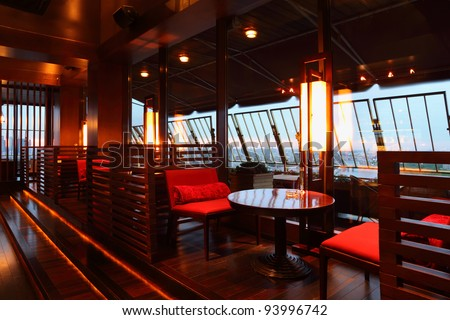 Row of brown tables and red seats with partition-walls in empty cozy restaurant at evening - stock photo