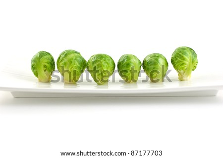 Row of brussel sprouts on long white plate isolated on white background - stock photo