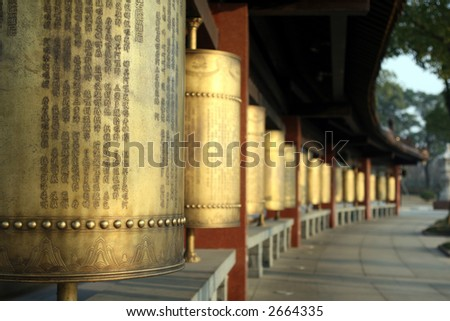 Row of Buddha copper prayer wheels. - stock photo