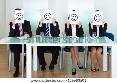 Row of business executives with smiley faces in front of their faces - stock photo