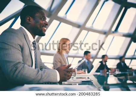 Row of business people listening to presentation at seminar with focus on African-American happy young man - stock photo