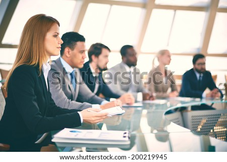 Row of business people listening to presentation at seminar with serious woman on foreground - stock photo