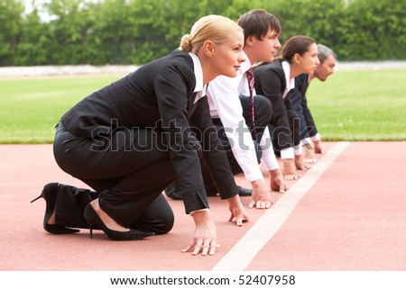 Row of business people looking attentively forwards before signal to run - stock photo