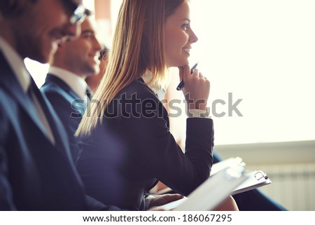 Row of business people making notes at seminar, focus on attentive young female - stock photo