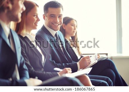 Row of business people making notes at seminar with focus on smiling young man - stock photo