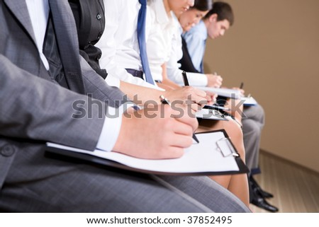 Row of business people making notes or writing business plan - stock photo