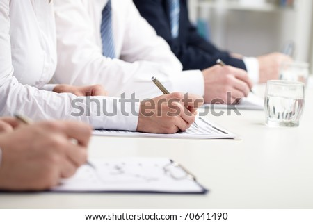 Row of business people?s hands writing - stock photo