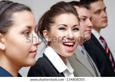 Row of business people with focus on cheerful businesswoman - stock photo