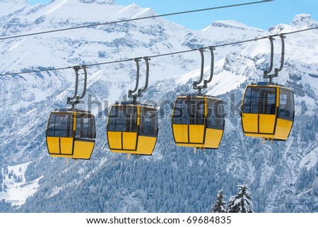 Row of cablecars against snowy swiss alps. January 2011. Switzerland - stock photo