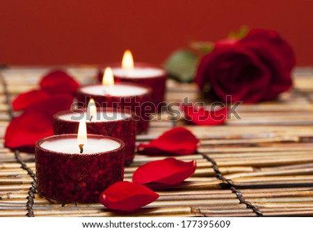 Row of candles with rose petals - stock photo