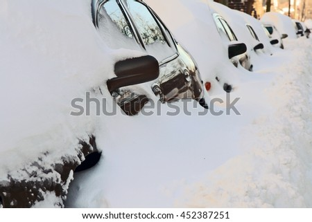 Row of cars covered by deep snow. Urban street after the heavy snowstorm. - stock photo