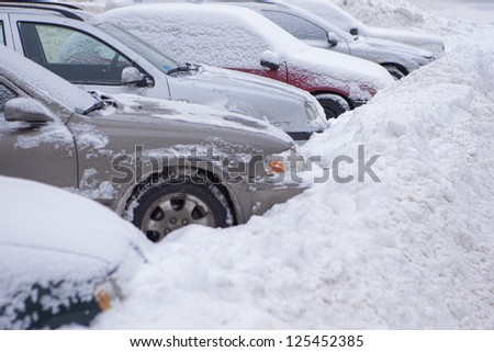 row of cars covered by snow in the eastern europe - stock photo