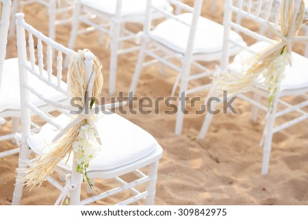 Row of chairs,which decorated by star fish,flowers and straw,on a sand beach for wedding ceremony.  - stock photo