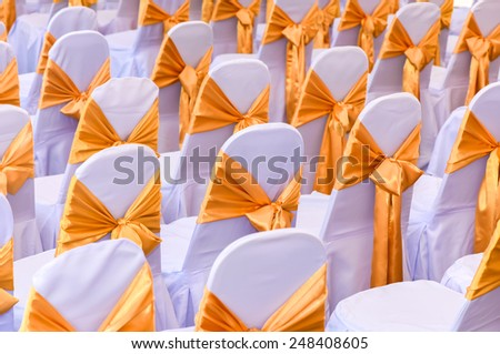 row of chairs with white cloth and yellow ribbons - stock photo