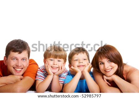 Row of cheerful family members lying and looking at camera with smiles - stock photo