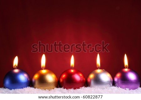 Row of christmas candles on red background