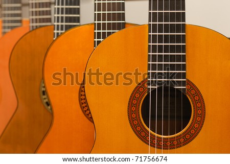 Row of classical acoustic guitars in musical store. Close-up view. - stock photo