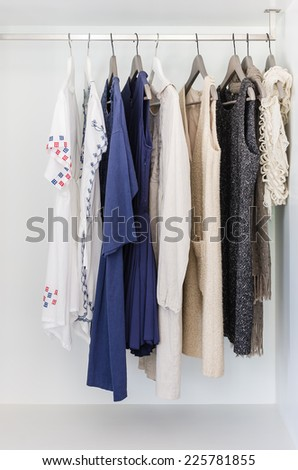 row of cloth hanging on coat hanger in wardrobe - stock photo