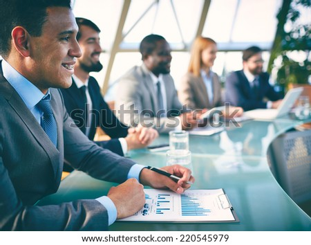 Row of co-workers listening to presentation at seminar with elegant young man on foreground - stock photo