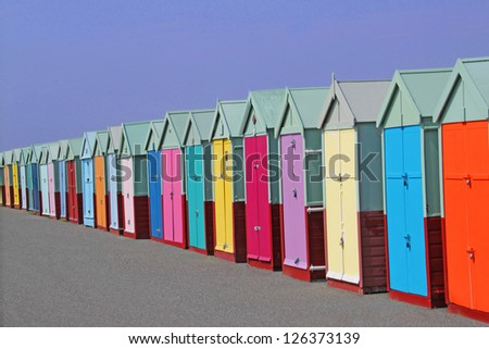 row of colored beach huts with blue sky background - stock photo