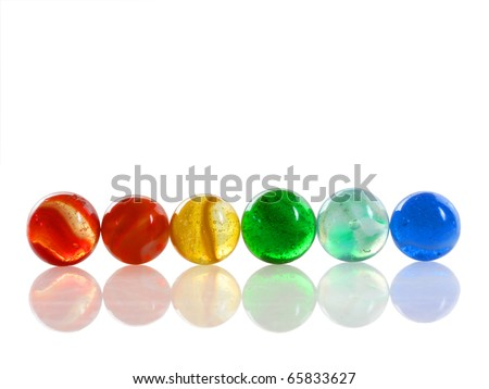 Row of 6 colorful antique marbles on a reflective white surface - stock photo