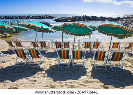 Row of colorful beach umbrellas and chairs - stock photo
