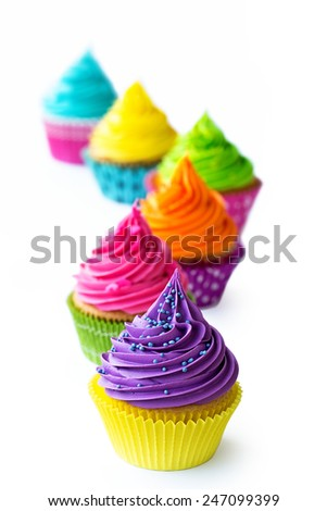 Row of colorful cupcakes against white - stock photo