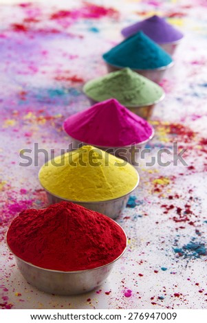 Row of colorful Holi powder in bows over white background