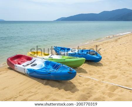 Row of colorful kayaks at sea shore - stock photo