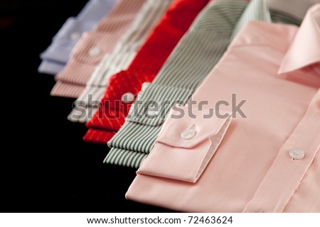 Row of colorful mens' shirts showing the cuffs - stock photo