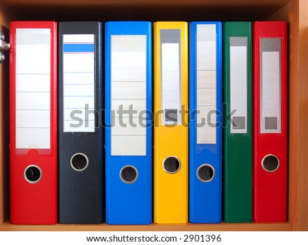 Row of colorful ring binders on shelf - stock photo