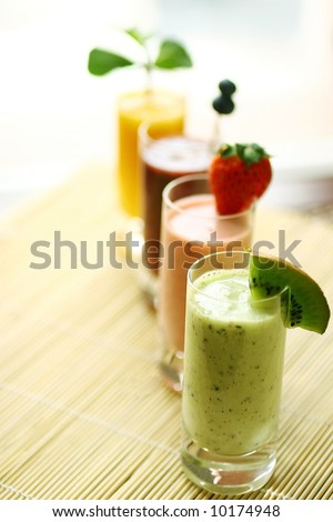 Row of colorful smoothies on a bamboo background - stock photo