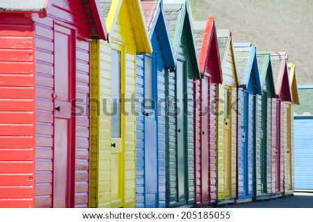 Row of colorful traditional wooden beach huts overlooking the Whitby Sands beach, Whitby, North Yorkshire, close up view receding from the camera - stock photo