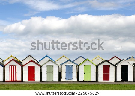 Row of colorful wooden beach huts, typical at English seaside. - stock photo