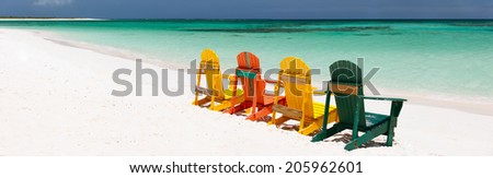Row of colorful wooden chairs at tropical white sand beach in Caribbean, panorama with copy space perfect for banners - stock photo